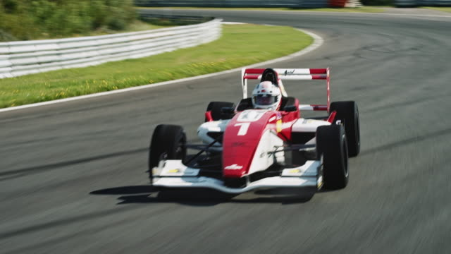formular one racing car driving on a racetrack - automobilismo video stock e b–roll