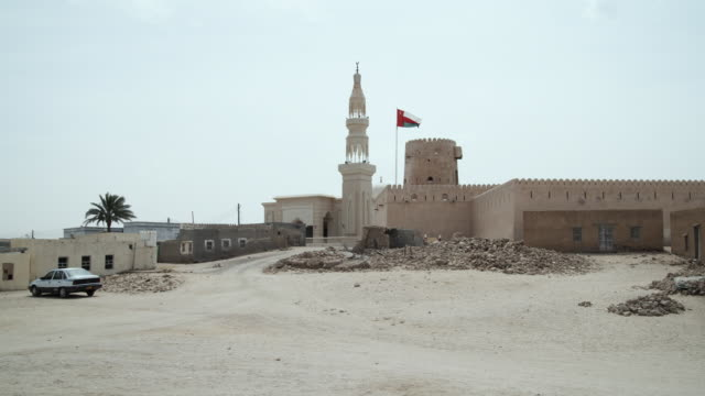 WS Fort and mosque with Omani flag blowing in wind, Ras al Hadd, Oman