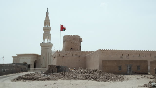 ws fort and mosque with omani flag blowing in wind, ras al hadd, oman - oman flag stock videos and b-roll footage