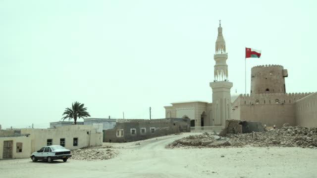 WS PAN Fort and mosque with Omani flag blowing in wind, Ras al Hadd, Oman