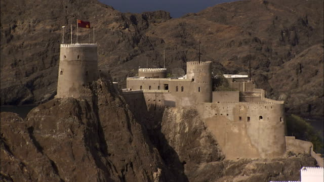 A fort sits on top of a rocky desert mountain near Muscat Harbour in Nizwa Oman. Available in HD.