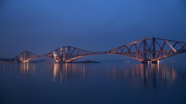 t/l, ws, forth rail bridge illuminated at dusk, edinburgh, scotland, united kingdom - fluss firth of forth stock-videos und b-roll-filmmaterial