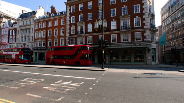 fortum and mason store closed at empty piccadilly with red double decker buses pass by during lockdown for coronavirus pandemic in london, england,... - red stock videos & royalty-free footage