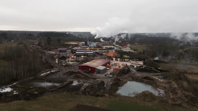 stockvideo's en b-roll-footage met forward aerial flight towards operating log sawmill factory with large chimney emitting smoke - boomstam