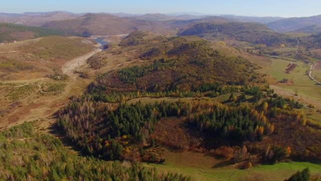vidéos et rushes de avant aérien au-dessus du petit village de montagne avec des maisons dispersées et des bois de forêt de mélèze orange en automne ensoleillé. vue aérienne de la route de montagne qui méandre entre les collines. - serbie