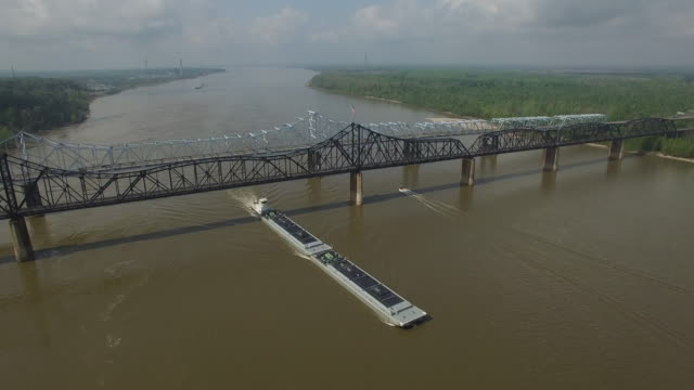forward over barge toward bridge - Drone Aerial 4K Mississippi river bridge and barge 1of14, everglades, gulf delta, new orleans, st louis, with cruise boats sailing and wildlife 4K Transportation