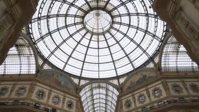 vídeos de stock e filmes b-roll de forward slow tilt-upward: sky dome of building reflecting the hot sun above the area of milan italy - claraboia