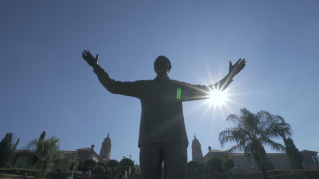 forward tilt-upward: the famous nelson mandela's statue standing tall in the middle of the green park - pretoria, south africa - statue stock videos & royalty-free footage