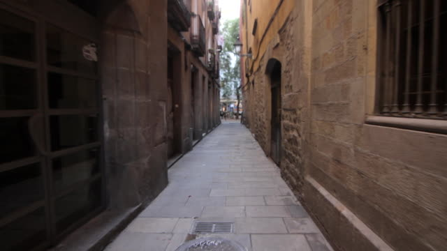 Forward tracking shot along a narrow alleyway in Barcelona.