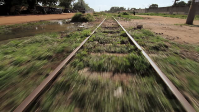 Forward tracking shot along a section of abandoned train line in Lome, Togo.