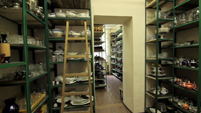 vídeos de stock, filmes e b-roll de forward tracking shot along the shelves of a film prop store. - antiquário loja