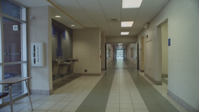 Forward tracking shot around an empty school hallway.