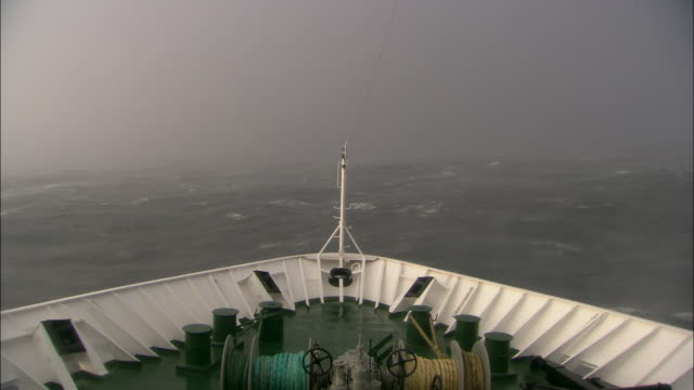 Forward tracking shot from the prow of a passenger ferry as it travels across rough water.