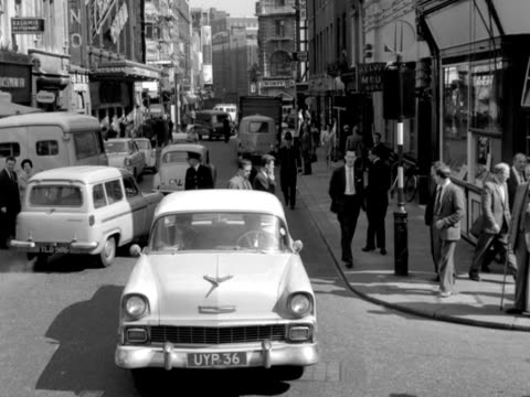 forward tracking shot from the top of a car moving along old compton street soho past shops and theatres towards the junction with rupert street - the past stock videos and b-roll footage