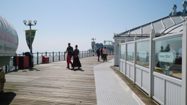 pov forward tracking shot moving along brighton's palace pier. - ブライトン パレスピア点の映像素材/bロール