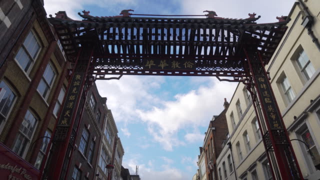 forward tracking shot moving underneath one of the decorative gates surrounding the chinatown district of london. - 門点の映像素材/bロール