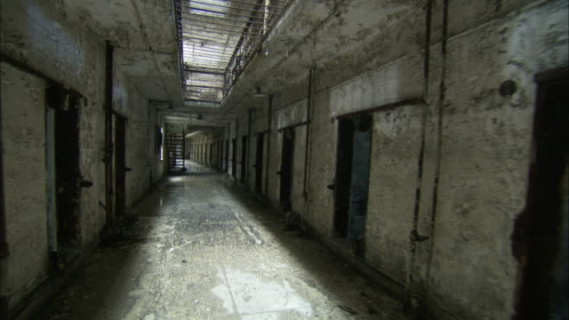 forward tracking shot past disused cells in an old prision wing at the eastern state penitentiary. available in hd - public building stock videos and b-roll footage