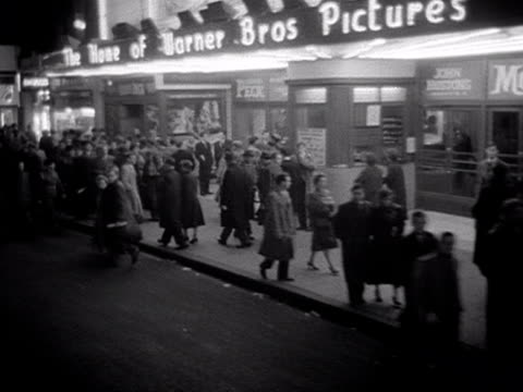 forward tracking shot towards leicester square moving past the neon signs for the warner theatre and towards the empire theatre. 1956. - ウェストエンド点の映像素材/bロール
