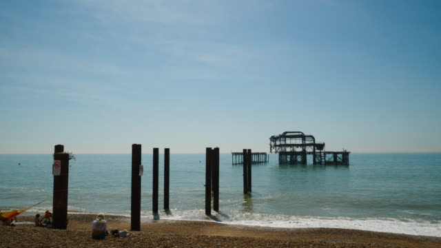 vídeos y material grabado en eventos de stock de forward tracking shot towards the derelict west pier on brighton beach. - marea