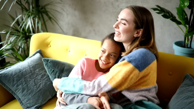 foster mom and foster daughter embracing and watching tv together - adoption stock videos & royalty-free footage