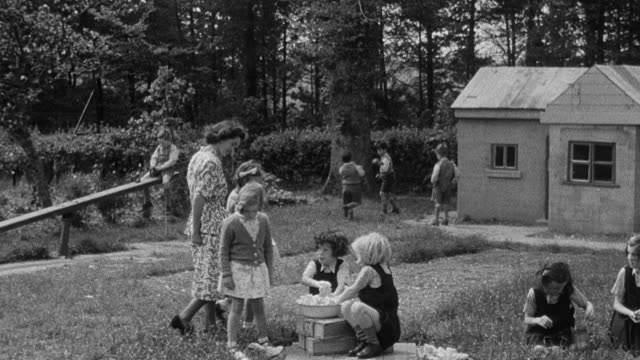 1950 ts foster mother walking with orphans among children playing in a yard / united kingdom - playhouse stock videos and b-roll footage