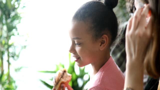 vidéos et rushes de parents adoptifs ayant le petit déjeuner dans le salon avec leur fille adoptive - famille d'accueil