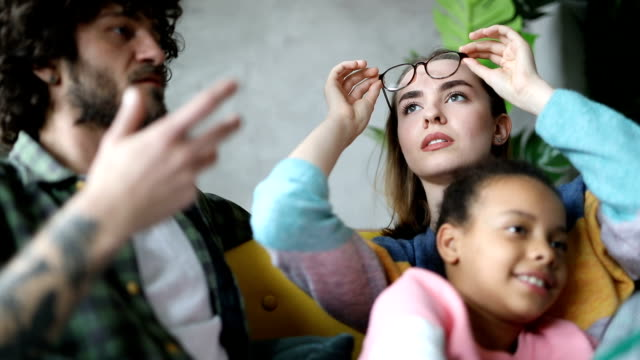 vídeos de stock e filmes b-roll de foster parents talking about eyewear and watching tv with foster daughter - acolhimento familiar