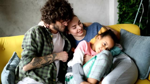 vidéos et rushes de parents adoptifs regardant la tv avec la fille adoptive - famille d'accueil