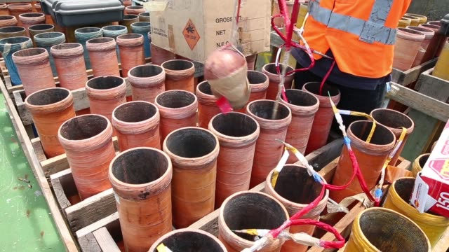 A Foti International Fireworks Pty employee places aerial shells for the Sydney New Year's Eve display into mortar tubes on a barge in Sydney...