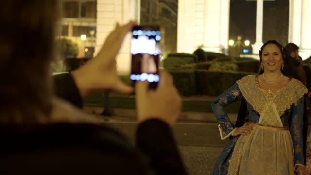 vídeos de stock, filmes e b-roll de foto con el teléfono móvil a una chica vestida de fallera - parte de una serie