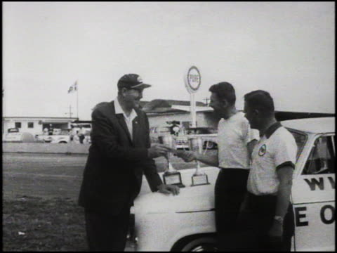 ws nascar founder bill france sr handing a check and then shaking hands with one of two members of the amc rambler team that won the 1960 pure oil... - circuito di daytona video stock e b–roll