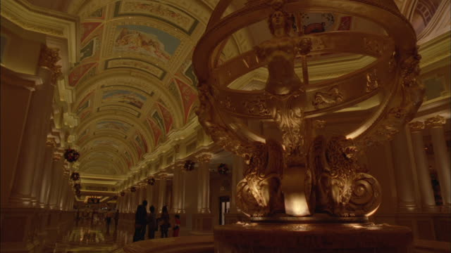 A fountain featuring a golden sphere stands in the center of an opulent rotunda.