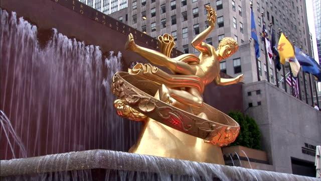 vídeos de stock, filmes e b-roll de a fountain flows near a gilded statue of prometheus at the rockefeller center in new york city. - centro rockefeller