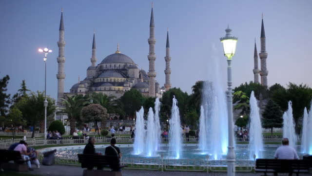 WS Fountain in Sultanahmet Park, Sultan Ahmed Mosque (Blue Mosque) in background, dusk / Istanbul, Turkey