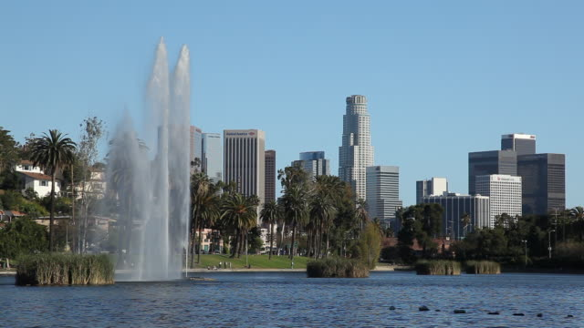 WS Fountain on pond in Echo Park with downtown skyscrapers in background / Los Angeles California, USA