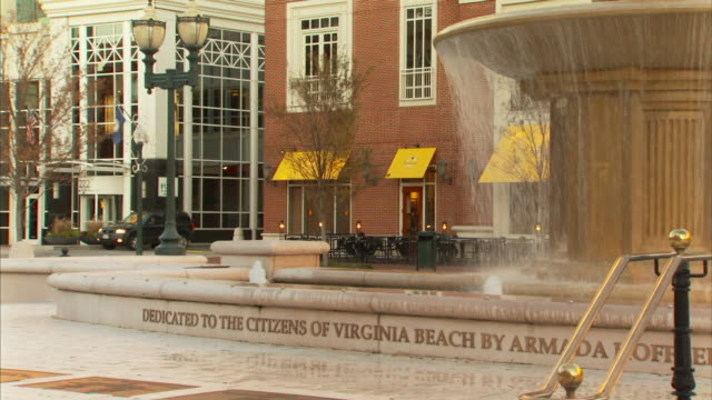 fountain pool w/ lettering dedicated to the citizens of virginia beach tall fountain pedestal w/ flowing water buildings bg - virginia beach stock videos & royalty-free footage