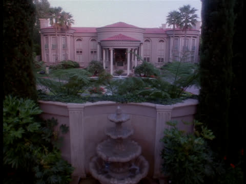 stockvideo's en b-roll-footage met a fountain spurts water into pools at the entrance of a spanish-style palatial mansion in los angeles. - spanish culture