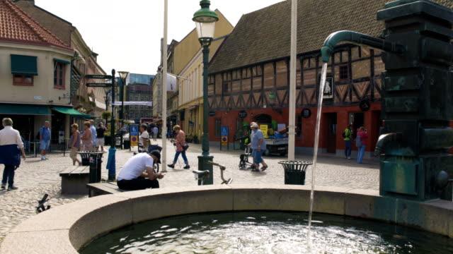 vídeos de stock e filmes b-roll de fountain well in malmö city square sweden - placa de nome de rua