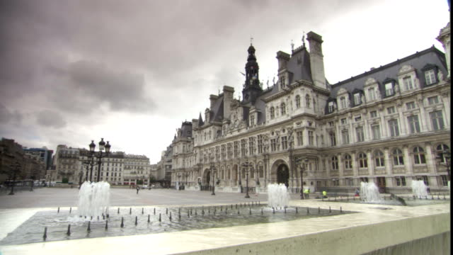 fountains splash in front of the hotel de ville in paris. - town hall stock videos & royalty-free footage