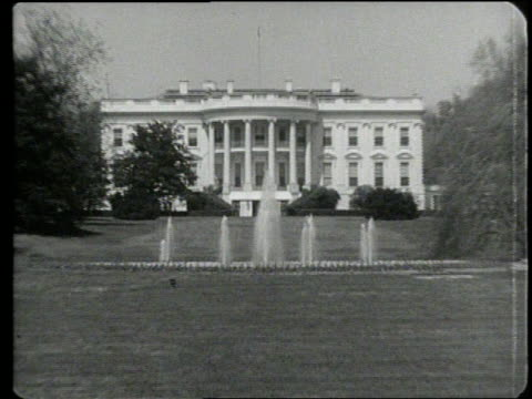 fountains spray in front of the white house president kennedy sits at his desk writing - 1960 stock-videos und b-roll-filmmaterial
