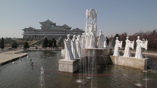 fountains spray water around several statues at the grand people's study house. - pyongyang stock videos and b-roll footage