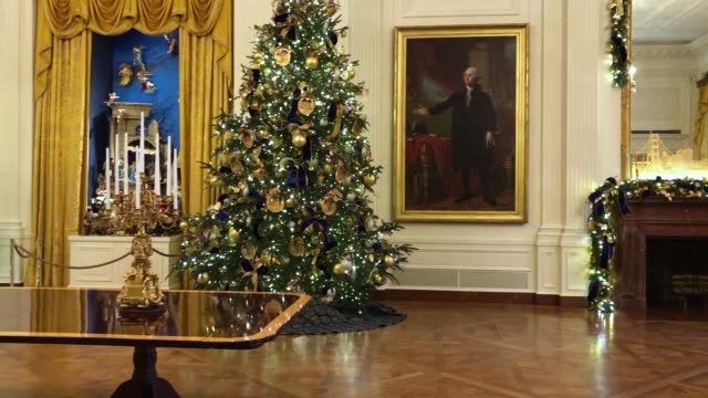 Four 14foottall Nobel fir trees decorated with 72 handmade paper ornaments representing six regions across America stand in the East Room of the...