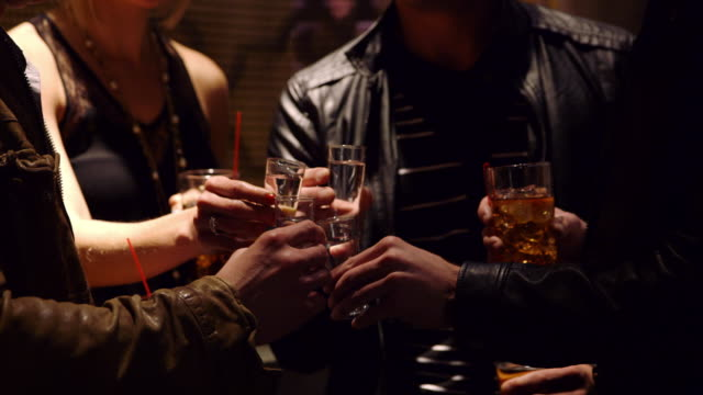 vidéos et rushes de cu four adults toasting shot glasses - whisky