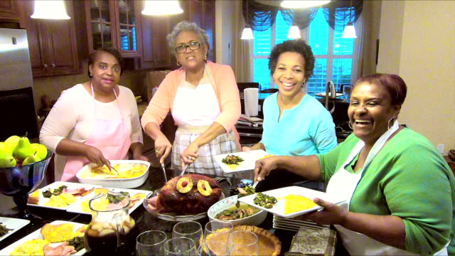 vídeos de stock e filmes b-roll de four african-american women serving their holiday meal - mulheres maduras