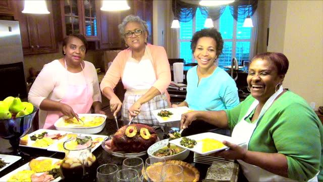vídeos y material grabado en eventos de stock de cuatro mujeres afroamericanas que sirve su comida navideña - pastel dulce