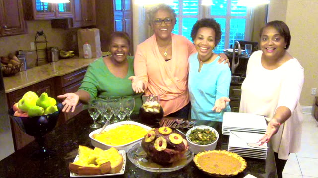 Four African-American women showing off homemade meal