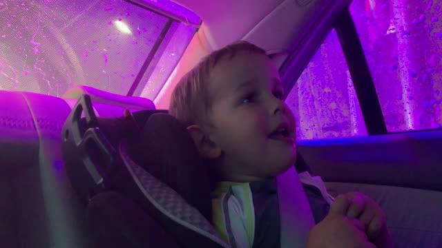 en fyra och en sex årig pojke leende, skratta och peka i baksätet på en bil som det går igenom tvål cykel av en drive-through biltvätt - biltvätt bildbanksvideor och videomaterial från bakom kulisserna