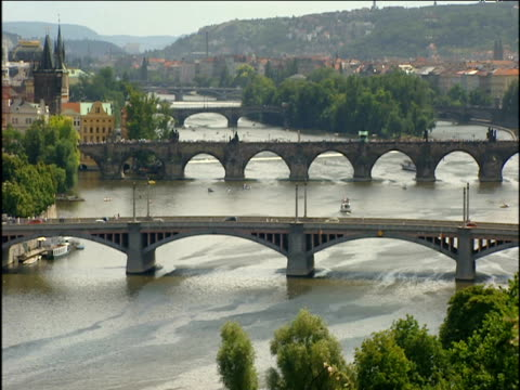 four arched bridges cross river vltava camera zooms out to overlook prague cityscape. - river vltava stock videos & royalty-free footage