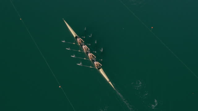 aerial four athletes rowing in a quad scull across a lake - competizione video stock e b–roll