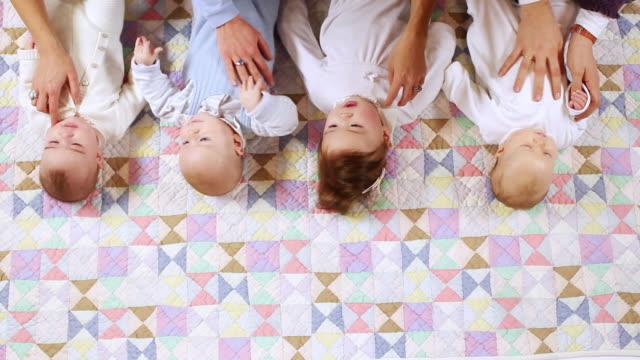 ms four babies (6-11 months) lying on fabric with mothers hands / brussels, belgium - 6 11 månader bildbanksvideor och videomaterial från bakom kulisserna